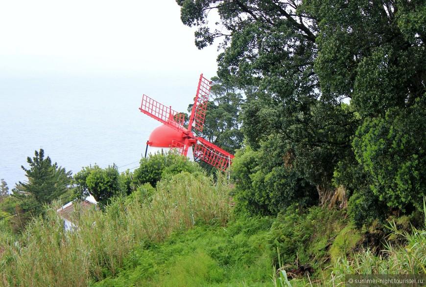 Красная мельница на зелёно-черно-белом острове.