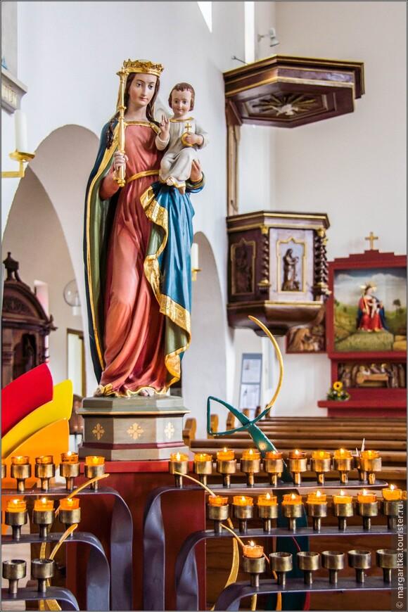 слева, ближе ко выходу их храма скуптура Девы Марии с младенцем на фоне кафедры и левого бокового алтаря