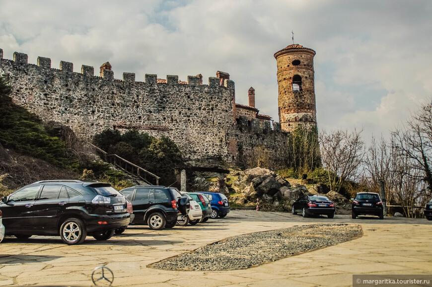 Перед входом в замок прсторная автостоянка