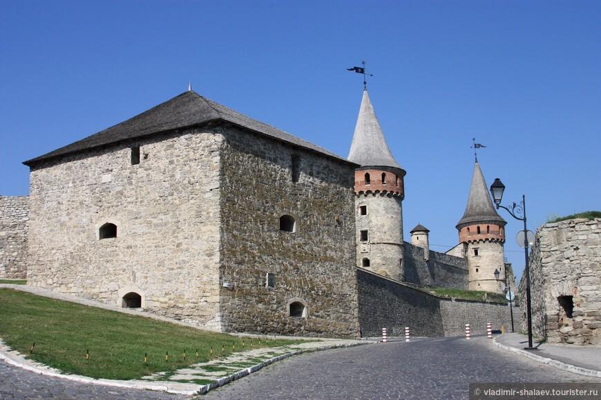 Перед замком дорога расходится. Правая идёт серпантином в обход замка, а левая идёт непосредственно в замок. Большая башня впереди - это новая Восточная башня. Следующая за ней -  Лянцкоронская башня. Следующая, которая вырастает из крепостной стены - это Камендантская башня, построена в начале XV века для дозора. И самая дальняя - башня Рожанка.