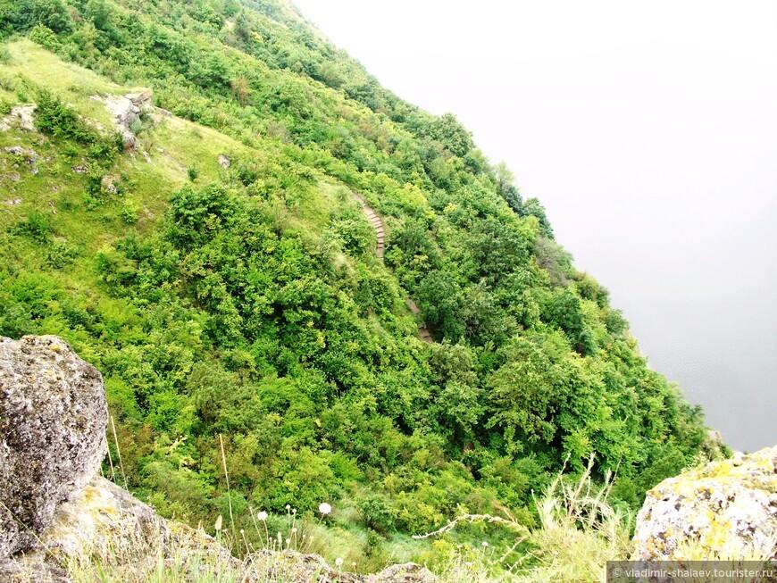 Вон по той узкой тропе, петляющей среди деревьев на склоне, можно спуститься с вершины Белой горы к остаткам древнего пещерного монастыря.
