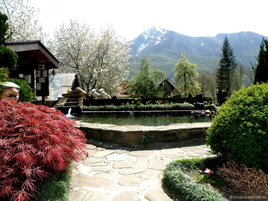 Это дворик в горном поселке. Верхушки гор в снегу, а у подножья цветут вишни, зацветает магнолия, клумбы пестрят разноцветьем!