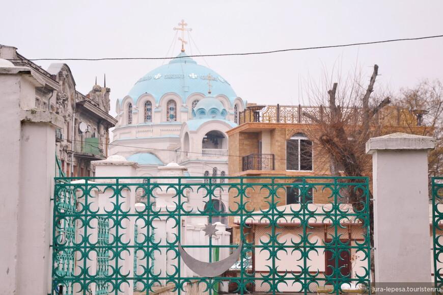 Вид на православный Свято-Николаевский собор сквозь ограждение мусульманской мечети Джума-Джами.