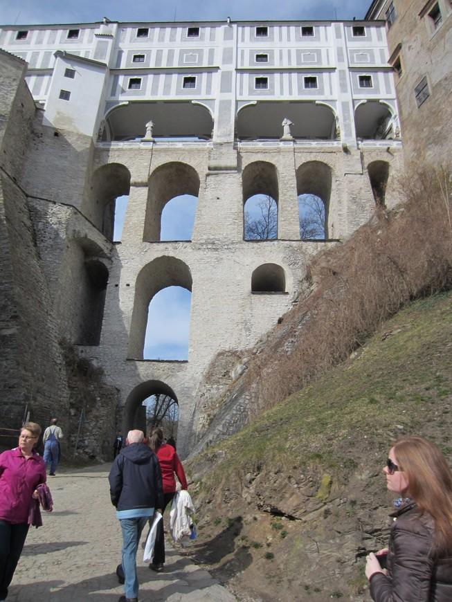Через западное крыло Замка в Чешском Крумлове проходит плащевой мост, построенный в 1764 году. Этот уникальный пятиэтажный мост через глубокий террасный ров соединяет Верхний город со зданием замкового театра и садами. Верхние два этажа моста являются крытыми коридорами, ведущими из дворца к театру и садам.