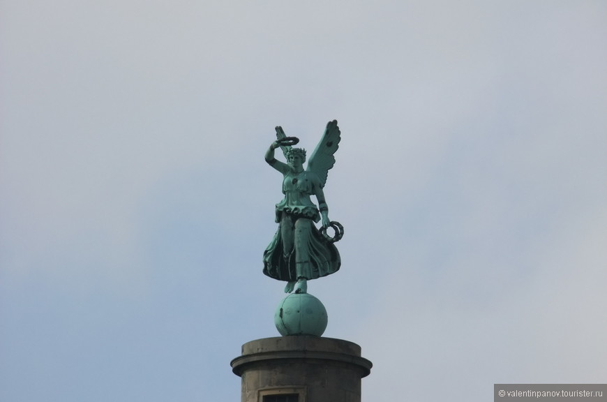 Колонну венчает шар со статуей богини победы Виктории.