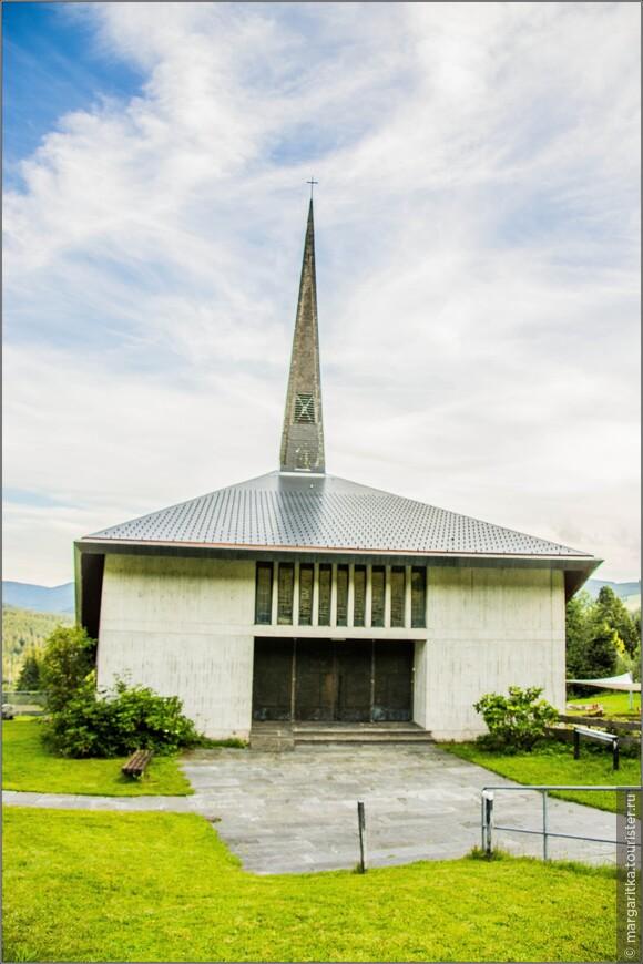 """Она была спроектирована архитектором из  Карлсруэ Райнером Диссе в начале 60-х.Первый камень в фундамент церкви был положен в 1963г. Церковь имеет свои истоки в часовне """"Мария Раст"""" в верхнем Фельдберге (Hof), которая была построена на фундаменте """"Фельдберг Фанни Майер"""".  Которая, в свою очередь, течение многих лет являлась Священным Сердцем часовни Каритас, бывшей домом для католиков Фельдберга, вплоть до строительства церкви Преображения Господня (St. Elisabeth – Falkau)."""