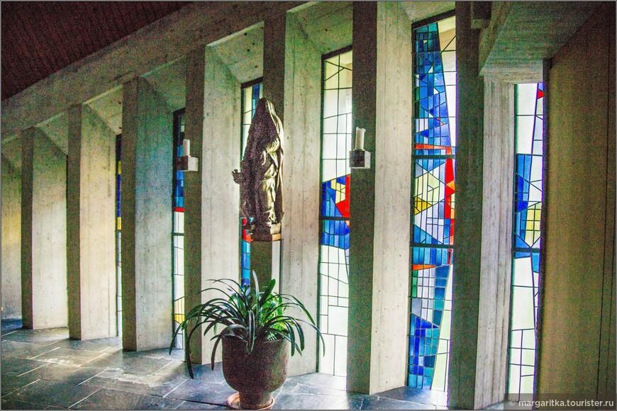 В конце правой стены с окнами-витражами единственная деревянная скульптура Мадонны с подросшим Христом