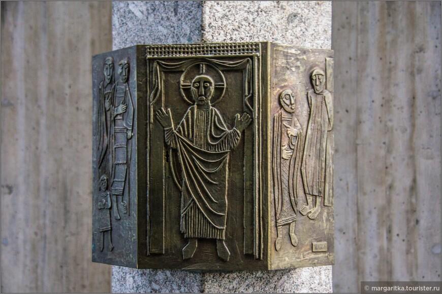 Справа от алтаря ромбовидный столб из гранита обрамлен медной чеканкой в стиле «наив»