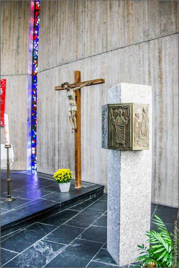 Единственным архитектурным крашением стены алтаря является красно-синий витраж в виде стержня с вкраплениями блестящего прозрачного стекла, символизирующий святую Троицу.