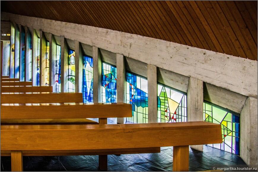 Окна выполнены из чередования узких бетонных колонн с витражами по всей высоте стен из абстрактных геометрических форм.