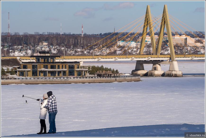 Вид на мост Миллениум. Пара пытается поймать палкой для селфи крохотного человека на льду Казанки.