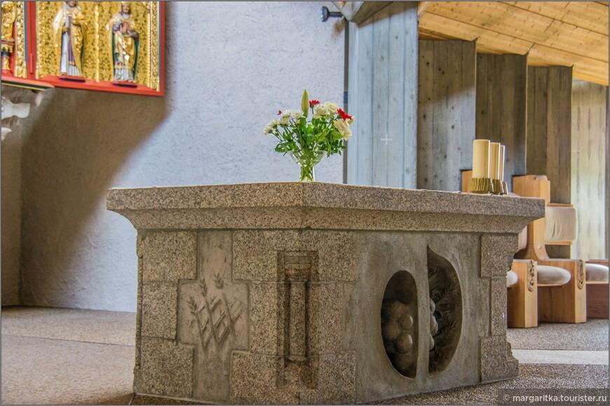 Для алтарного стола из алтаря старой церкви были взяты угловые элементы и плиты, в то время как боковые панели были обновлены идеей винограда и пшеница, напоминающими евангелическое таинство превращения хлеба и вина в Евхаристии.