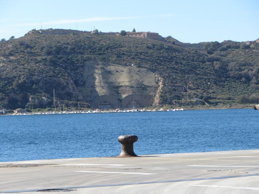 Город несколько столетий был базой испанского флота.  И в наши дни там находятся базы испанских и натовских кораблей и подлодок. Кроме того, естественно, есть грузовой и пассажирский порт. В итоге в 200-тысячном испанском городе не нашлось места пляжу! :) На фото - на том берегу тоннели\ангары для подлодок, сейчас правда неиспользуемые