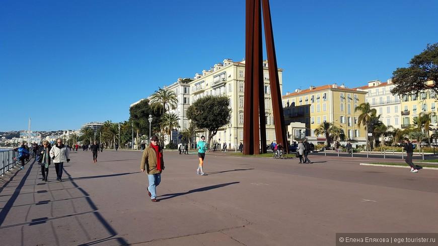 Знаменитая Английская набережная, на которой в воскресный день много людей на велосипедах и занимающихся бегом и спортивной ходьбой. Темная колонна - это памятник, символизирующий объединение французских провинций. Памятник заканчивает перпендикулярную набережной эспланаду Жоржа Помпиду (Esplanade Georges Pompidou) .