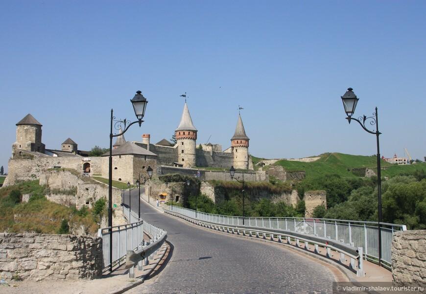 Замковый мост, соединяющий Старый город с крепостью, с виду выглядит как сплошная каменная стена, однако на самом деле представляет собой своеобразный саркофаг, содержащий внутри более раннее сооружение. По одной из версий, в основе нынешнего моста находится сооружение римской эпохи. Первоначально Замковый мост был арочным. Он построен над каньоном Смотрича в том месте, петля реки образует тонкий скалистый перешеек, отделяющий Старый город от материка. Говорят, что это единственный в мире мост, построенный вдоль, а не поперек русла реки. Нынешний вид Замковый мост обрел в XVII в., когда Каменец-Подольский захватили турки. Они перестроили мост, использовав камень от разобранного монастыря Босых Кармелитов. С тех пор его часто называют Турецким мостом.