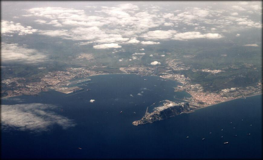 Испанский город Альхесирас (слева) и Гибралтар (справа) — заморская территория Великобритании, оспариваемая Испанией, на юге Пиренейского полуострова, включающая Гибралтарскую скалу и песчаный перешеек, соединяющий скалу с Пиренейским полуостровом.