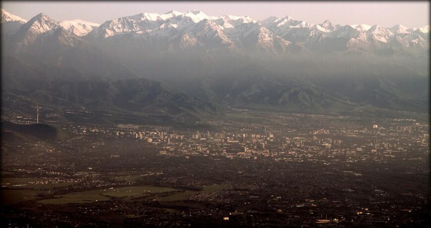 Город Алматы на фоне горного хребта Заилийский Алатау (расположен на северо-западе Тянь-Шаня).