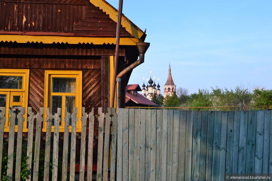 Современный деревянный хозяйский дом, а вдали поразительный силуэт старины. Кажется до колокольни Антипиевской церкви и рядом стоящей пятикупольной Лазаревской идти да идти.