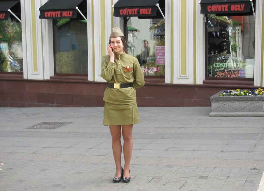 В Столешниковом переулке мы встретили девушку в форме. Увидев наведенный на неё фотоаппарат,  остановилась, зажмурившись от солнца. В  городе уже начинается празднование Дня Победы.