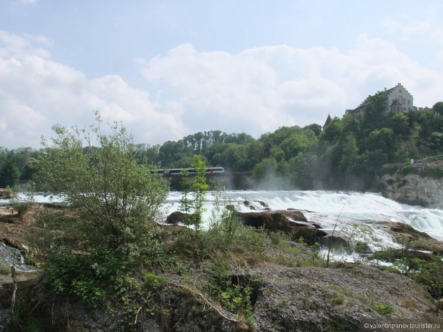 А вот и сам Рейнский водопад! Он расположен в верхнем течении Рейна, в швейцарском кантоне Шаффхаузен, рядом с городком Нойхаузен. Наряду с более высоким, но менее полноводным водопадом Деттифосс в Исландии, Рейнский водопад является самым большим водопадом в Европе. Высота водопада — 23 м, ширина — 150 м. Как-то с этой точки обзора он не очень похож на один из крупнейших. На заднем фоне - скоростной поезд. Вероятно, из окна поезда виды более живописны!