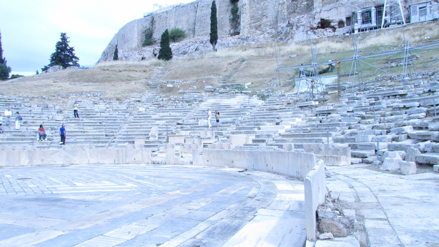 Поднимаясь на скалу Акрополя, прежде всего оказываешься в древнем театре Диониса. Сидя на этих каменных  скамьях (койлонах) древние афиняне сопереживали героям Софокла и Еврипида, хохотали над шутками Аристофана.