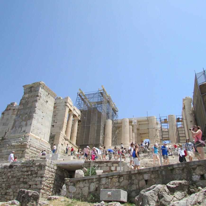 Чем выше поднимаешься, тем больше людей встречаешь на своем пути.  Множество экскурсионных групп, возглавляемых своими гидами, направляется ко входу в Акрополь. Очередной поворот выводит к мраморной лестнице Пропилей.