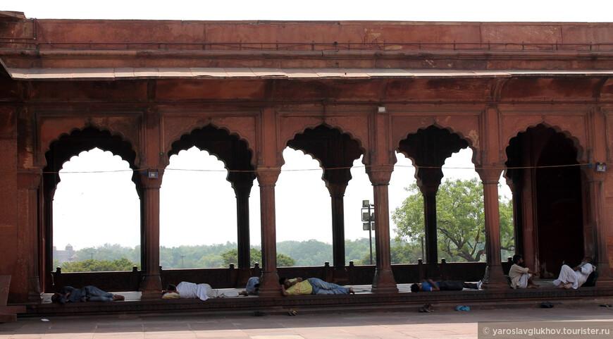 По периметру мечети люди отдыхают в тенёчке.