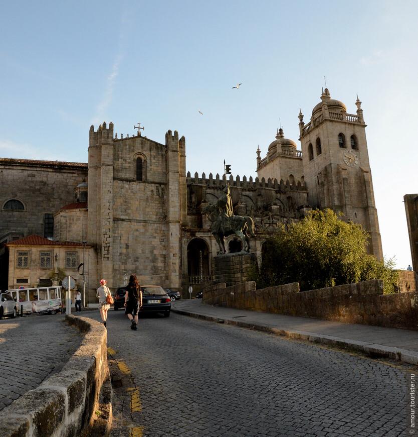 Ближе к вечеру мы пошли прогуляться к реке. По пути прошли мимо Кафедрального собора Порту. Кафедральный собор Порту - был построен в 12 веке, не только как церковь, но и как крепость. Расположенный на холме над рекой Доуро, раньше он был окружен защитными городскими стенами. Перед собором - памятник Вимаре Перешу, первому графу Португалии, установленный к 1000 летию Португалии.