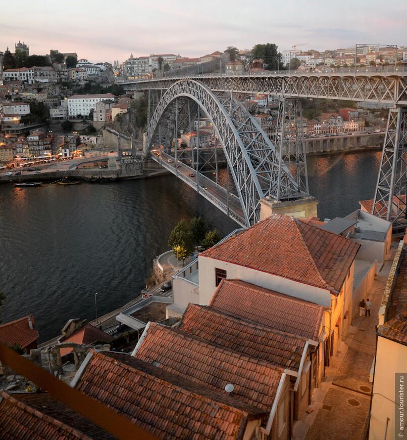 Внизу под вагончиком фуникулера склады портвейна и дальше красавец мост Понте-де-Дон-Луиш с его двумя частями: железнодорожной и пешеходной и автомобильной. Первая связывает верхний город с холмами Вила-Нова-де-Гайя. А автомобильная соединяет район Рибейра с винными подвалами Вила-Нова-де-Гайя.