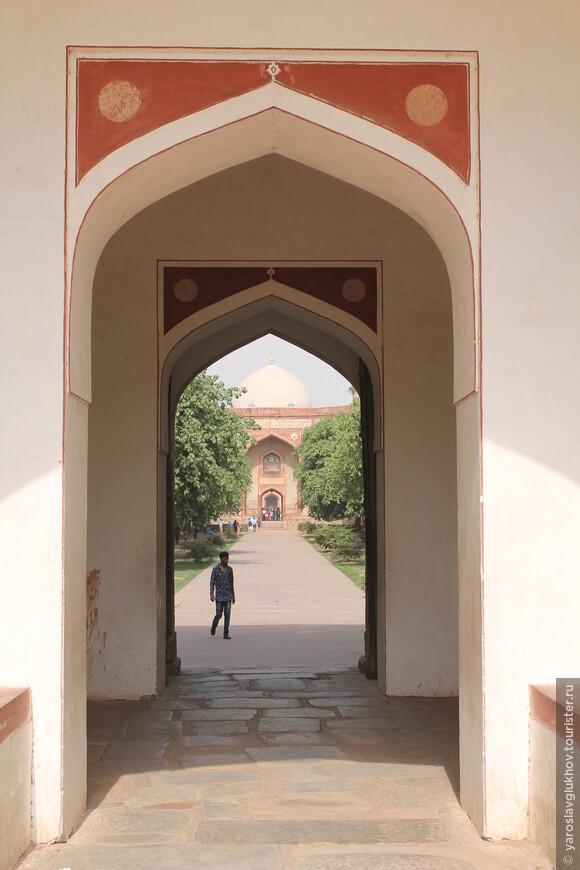 Через арку в воротах уже видны ворота и купол мавзолея.