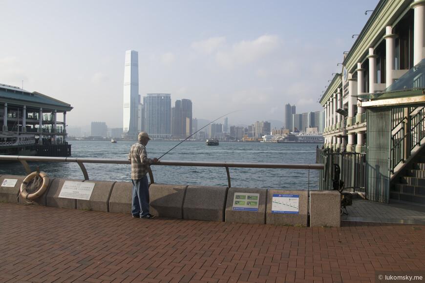 Мужик ловит рыбу у  пирса в далеке самое высокое здание Гонконга