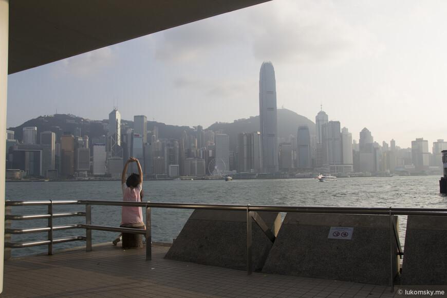 Девчонка  отдыхает, любуется на набережную и на второе по величине здание Гонконга