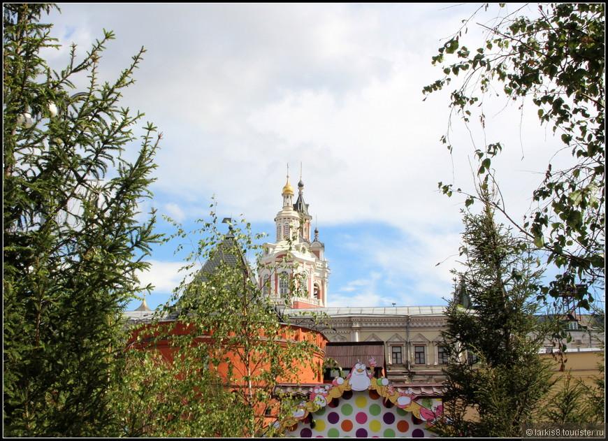 Очень непривычный вид центра города, сквозь зелень деревьев.