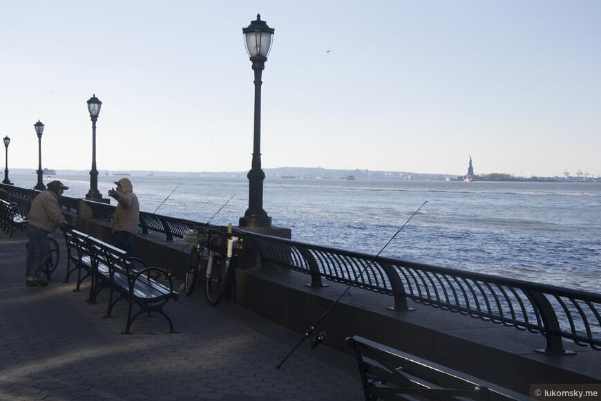 Рыбаки ловят рыбу напротив статуи свободы