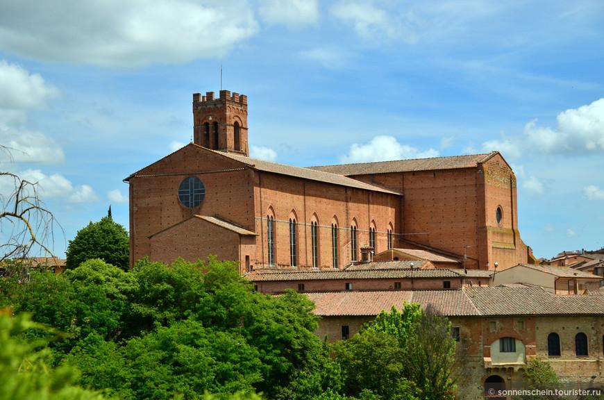 Внушительная и суровая базилика Сан-Доменико — одна из важнейших церквей Сиены. Именно эту массивную постройку из красного камня с невысокой зубчатой башней вы видите на холме, когда подъезжаете к городу со стороны крепости Медичи. Похожая на старинный рыцарский замок базилика — это доминанта переднего плана в панораме города, в то время как акцентом второго плана стал далекий Дуомо.