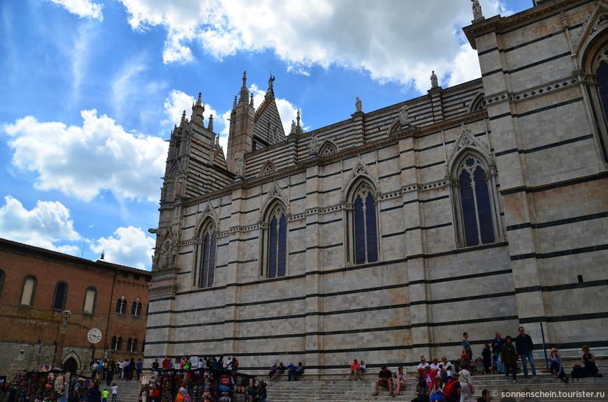Сиенский кафедральный собор, расположенный на Соборной площади, возвышается не только над площадью, но и над всем городом. На этом месте первоначально был античный храм, посвященный Минерве, затем римская крепость с четырьмя башнями, одна из них впоследствии была преобразована в колокольню.