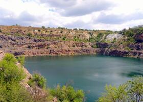 """Люди добывали гранит, трудились и радовались. Но в одну """"прекрасную"""" ночь дно кратера разверзлось, оттуда хлынула вода и затопило карьер вместе со всей техникой. Так образовалось это Черное озеро. Его второе название - Радоновое озеро, также известное как """"Черное море"""", возникло на месте старого гранитного карьера на территории регионального ландшафтного парка """"Гранитно-степное Побужье"""" рядом с порогами Южного Буга. Озеро глубиной более 40 м с отвесными берегами питается подземными радоновыми источниками. Вода в нем очень чистая, имеет необычно яркий голубой цвет. По легенде, на дне можно увидеть затопленный экскаватор. Над озером оборудована удобная смотровая площадка."""