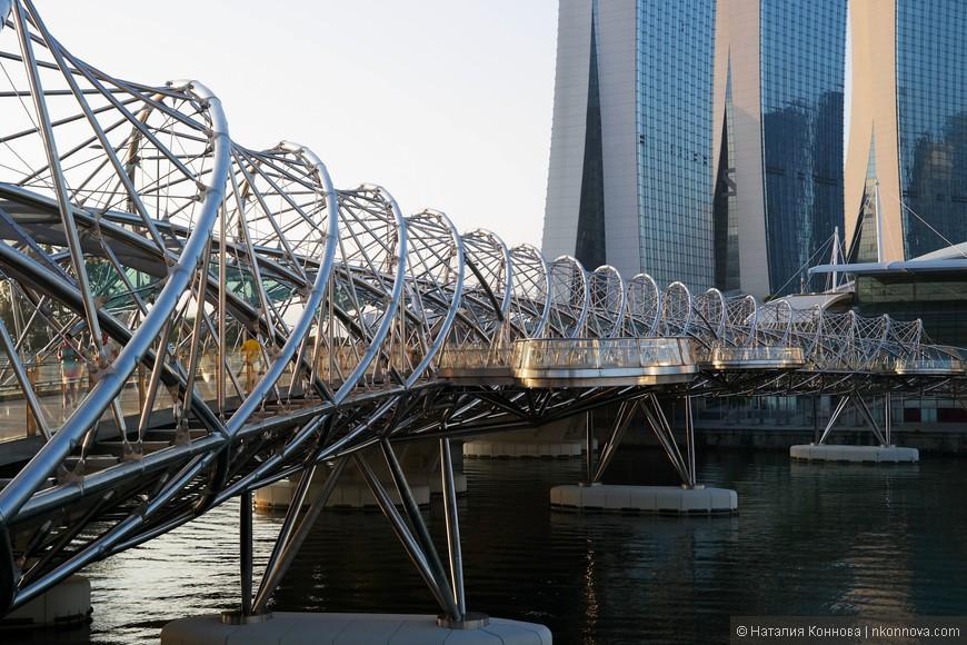 Пешеходный мост Helix Bridge (Double Helix) имитирует внешне спираль ДНК. Очень необычно, конечно. По внутренней части спирали даже предусмотрена небольшая защита от солнца и дождя.