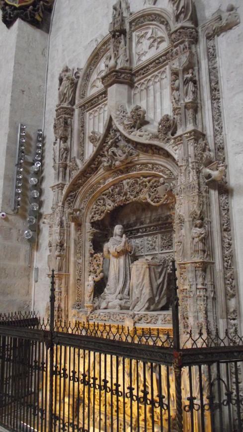 Cartuja de Miraflores. Могила Инфанта Альфонсо Кастильского, брата Изабеллы I Католической. Инфант Альфонсо Кастилии умер в 14 лет, 5 июля 1468 в городке Карденьос близ Авилы. Он был похоронен в монастыре Сан-Франциско в Аревало, где его тело пребывало до 1492, когда королева Изабелла I приказала перевезти его останки в Картезианский монастырь Miraflores. Могила инфанта Альфонсо Кастилии расположена в левой стороне клироса церкви Картезианского монастыря Miraflores. Она полностью вырезана из алебастра и имеет форму стрельчатой арки с зазубренной аркадой. Могила как бы вставленна в рамку из двух пилястров, украшенных образами апостолов и святых, и завершена рельефом Благовещения. Только за один алебастр, привезенный из предместий Гвадалахары, монастырю пришлось выложить 158.252 старинных испанских монет.