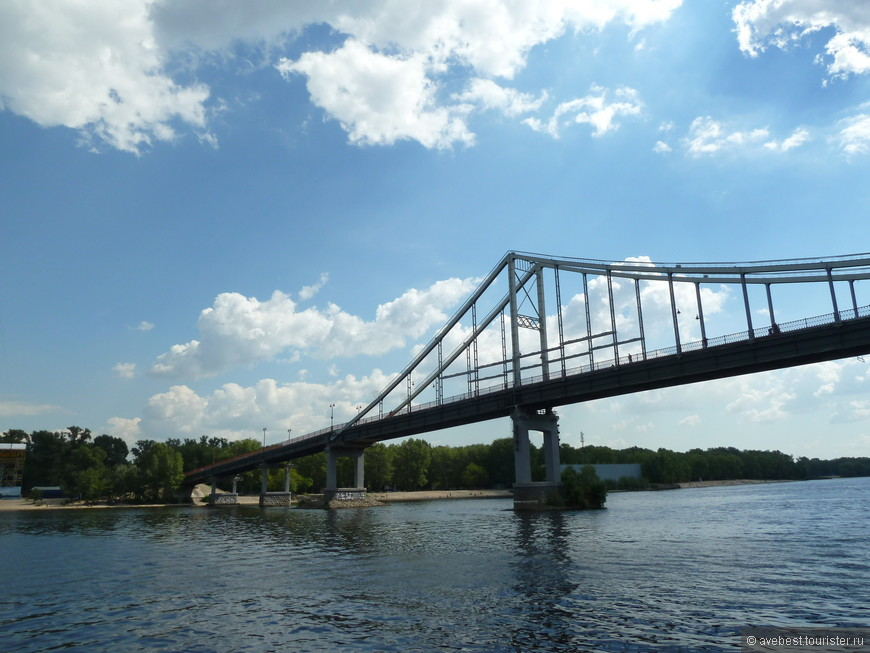 """По конструкции — цельносварной мост, возведённый с использованием автоматической сварки. Общая длина моста — 429 м, основной пролёт — 180 м, ширина пешеходной части — 7 м. Состоит из трёх центральных пролётов висячего типа и береговых участков балочной конструкции. Центральные пролёты по схеме 60 + 180 + 60 м подняты над уровнем реки на 26 м, что обеспечивает проход судов при наивысших уровнях воды. Гиперболические по профилю и жёсткие по конструкции цепи (сваренные из металлических листов) закреплены на двух пилонах рамной формы высотой 32 м. Вертикальные подвески по обеим сторонам дороги с шагом 10 м изготовлены из стальных угольников. Дорожное полотно из железобетонных плит опирается на две двутавровые сварные балки (высота 2,4 м). Береговые части выполнены в виде балочных стале- железобетонных пролётных строений: на левобережном участке — три пролёта по 36 м, на правобережном — один пролёт длиной 17,9 м. Опоры моста железобетонные, рамной конструкции. Основы всех опор — железобетонные забивные сваи (сечение 35 × 35 см, длина от 9 до 13 м).  Выразительный силуэт моста стал одним из традиционных элементов в панораме Киева. <noindex><noindex><a href=""""https://www.tourister.ru/go?url=https://ru.wikipedia.org"""" class=""""ext_link"""" target=""""_blank"""">https://ru.wikipedia.org</a></noindex></noindex>"""