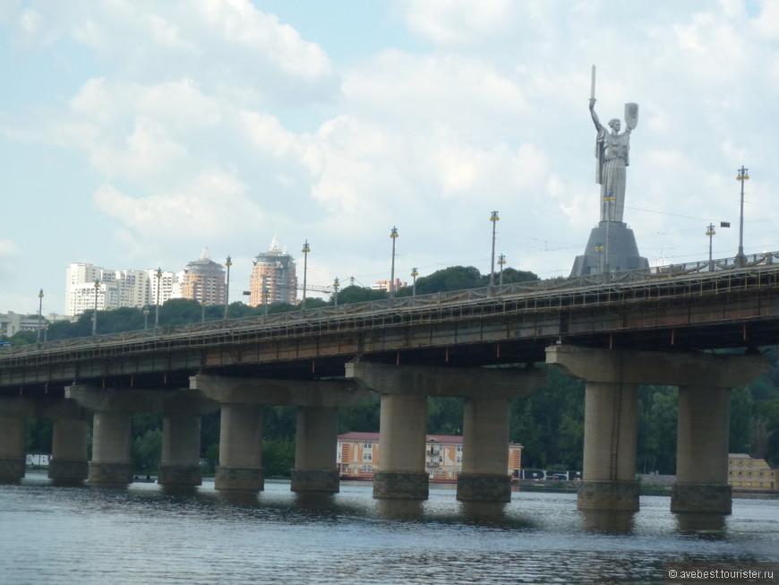 """Мост имени Е. О. Пато́на. Мост балочной конструкции, со сплошными главными балками двутаврового сечения длиной 58 и 57 м, высотой 3,6 м, 26-пролётный, с опорами на кессонной основе. Пролётные строения состоят из 264 однотипных блоков длиной 29 м, во время монтажа которых было сварено 10668 м швов. Ширина проезжей части 21 м, ширина тротуаров — по 3 м. Для увеличения безопасности движения в 1968 году на мосту Патона было устроено полужесткое декоративно-художественное ограждение (впервые в СССР). Его выполнило предприятие из г. Донецка """" Ремкоммунэлектротранс"""" . С 1 ноября 1954 года и до 9 июня 2004 года по мосту проходила трамвайная линия. <noindex><noindex><a href=""""https://www.tourister.ru/go?url=https://ru.wikipedia.org/wiki/%D0%9C%D0%BE%D1%81%D1%82_%D0%9F%D0%B0%D1%82%D0%BE%D0%BD%D0%B0"""" class=""""ext_link"""" target=""""_blank"""">https://ru.wikipedia.org/wiki/Мост_Патона</a></noindex></noindex>"""