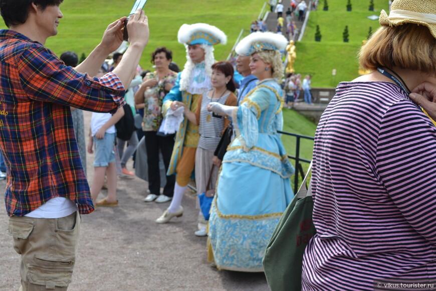 """Около фонтанов фланируют дамы и господа в нарядах петровских времен. С ними можно сфотографироваться за деньги. Желающих немало. Смущает загар на лицах """"благородных"""" дам - шутка ли, целый день на солнце!"""