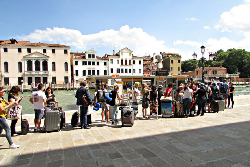 Очередь на остановке вапоретто. Люди с чемоданами - это туристы, прибывшие в Венецию на поезде, ведь отсюда рукой подать  до вокзала Санта Лючия. Как я уже писал, в 2014 г. мы плавали по Гранд-каналу на водном такси. Это достаточно дорогое удовольствие - за сорокаминутную поездку приходится выкладывать по 30 евро с человека. А увидеть получается совсем немного -  успеваешь прокатиться только  от Сан-Марко до Риальто и обратно. На вапоретто можно проплыть по всему городу, и это обойдется значительно дешевле. Одна поездка - 6 евро с человека. Но можно купить за 20 евро дневную карту и беспрепятственно переходить с одного маршрута на другой. Это удобнее в том плане, что не всегда сходу можно разобраться  какое вапоретто швартуется в нужном тебе месте. Пройдя за турникет, понимаешь, что тебе надо на другой причал. Каждая такая ошибка будет стоить 6 евро с человека. А с суточной картой можно ошибаться сколько душе угодно.