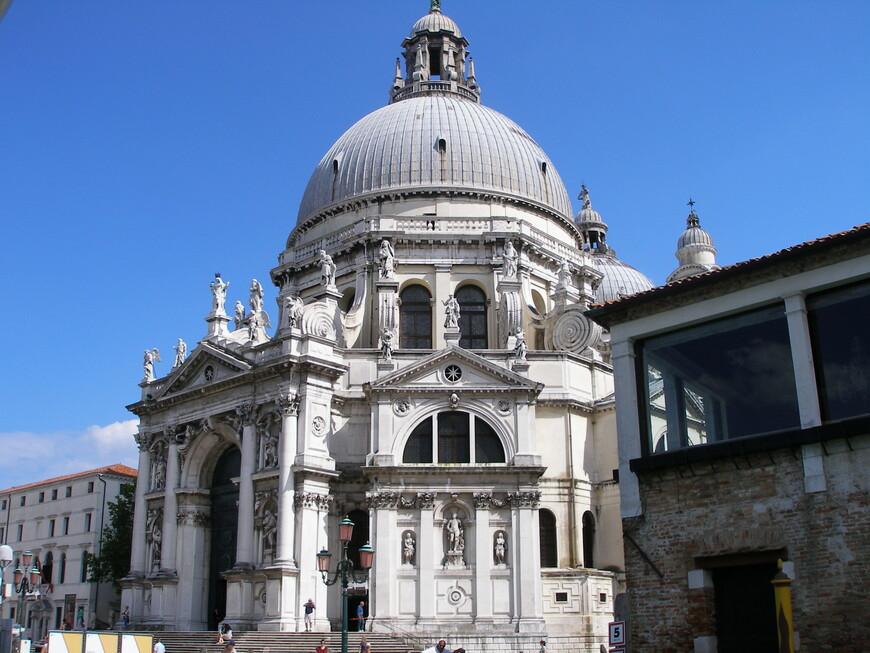 """Собор Санта-Мария делла Салюте. Решение о ее постройке в 1631 г. принял сенат в благодарность Богоматери за прекращение эпидемии чумы. Некоторые называют эту барочную церковь """"свадебным тортом"""", другие - """"самым красивым храмом Венеции""""."""