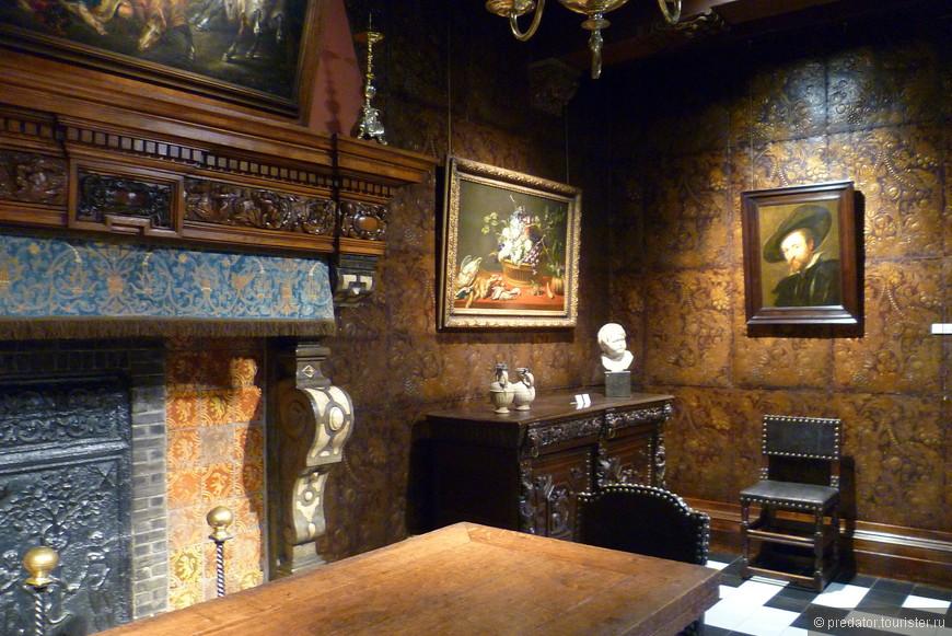 """Внутри самого дома реконструирована обстановка XVII века: мебель, изразцы на кухне, обои из позолоченной кожи, подсвечники. Открыты для посещения большая мастерская, кухня, столовая, две бывшие спальни, гостиная и другие комнаты, включая кунсткамеру Рубенса с его личной коллекцией произведений искусства.  На стене справа картина """"Автопортрет""""."""