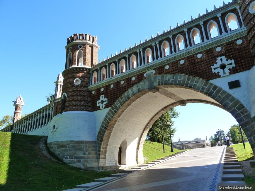 """Фигурный мост, построенный в 1776—1778 годах по проекту Баженова, является продолжением Берёзовой перспективы, идущей от Большого моста через овраг к Малому и Среднему дворцам, соединяя её северную и южную части. С западной стороны парка, при движении по Аллее через плотину между прудами, мост воспринимается как въездные ворота. Сейчас это главная аллея, ведущая к дворцовому комплексу; в XVIII веке — второй парадный въезд на территорию Царицына. Баженов выбрал необычайно выигрышное местоположение для постройки: мост, расположенный на крутом склоне холма, скрывает панораму центральной части дворцового комплекса. Такое расположение обеспечивает эффект внезапности раскрытия дворцовой панорамы перед взором посетителя, проходящего под мостом. Со стороны дворцовой площади благодаря рельефу местности от моста видна лишь его верхняя часть: постройка, казавшаяся монументальной со стороны прудов, отсюда воспринимается лёгкой декорацией с башенками. <noindex><noindex><a href=""""https://www.tourister.ru/go?url=https://ru.wikipedia.org/wiki"""" class=""""ext_link"""" target=""""_blank"""">https://ru.wikipedia.org/wiki</a></noindex></noindex>"""