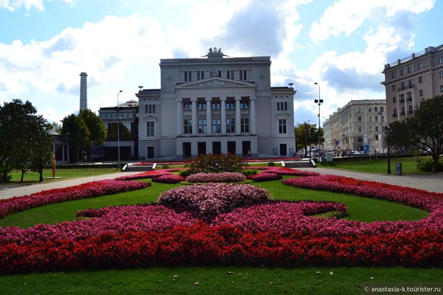 Здание национальной оперы находится в самом начале центрального парка Кронвальда. Здесь очень красиво: цветы, фонтаны, мост через реку. Напротив оперы памятник Лиепе и мэру города с его женой и собачкой.