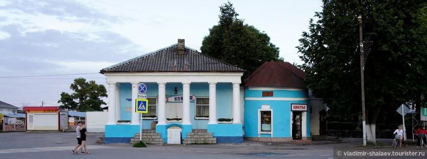 Памятник архитектуры - дом с портиком. Построен в первой половине XIX века . Судя по старой фотографии ниже в здании размещался мануфактурный магазин Гиндина.