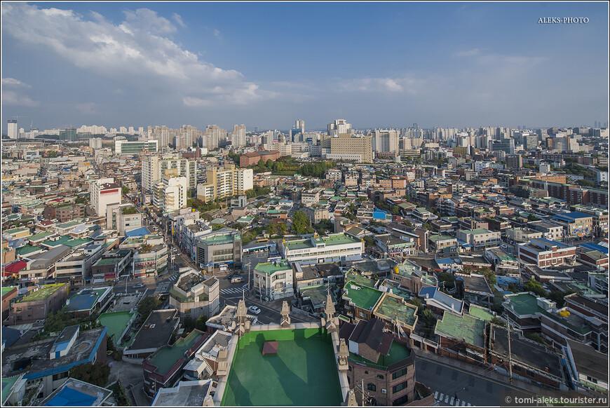 Я уже говорил, что с архитектурной точки зрения Сувон особо ничем не отличается. Поэтому с высоты десятиэтажный, стоящей на холме, мы увидели россыпь зеленых плоских крыш частного сектора - на переднем плане. И типичные многоэтажки микрорайонов - на заднем плане.