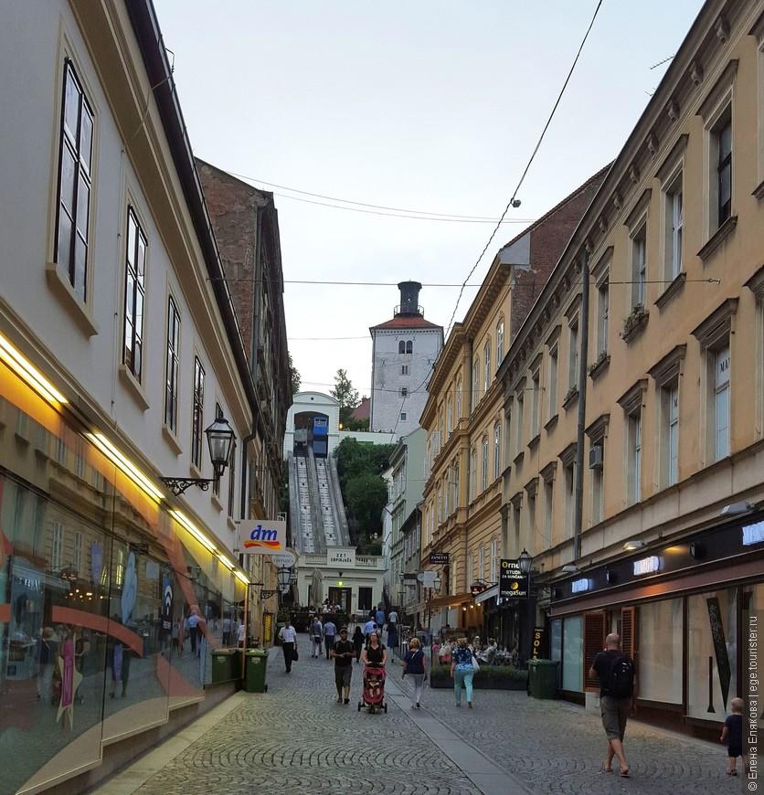 Загреб — это город на двух холмах: нижнем холме (церковный Каптол) и верхрем холме (светский Градец, Верхний город, или Горний град). Это поворот с улицы Илицы к фуникулеру, на котором можно подняться в Градец, видна башня Лотршчак в Верхнем городе, пушечный выстрел с которой производится каждый полдень.